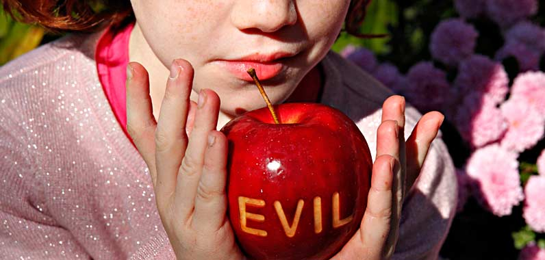 little girl holding an apple laser etched with the word evil